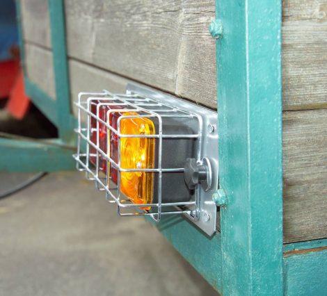 Háromkamrás hátsó fényszóró, védőráccsal és rendszámvilágítással.